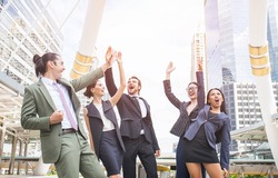 Small group of business people outside their company, holding hands raised celebrate business success.