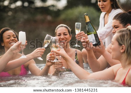 Small group of female friends socialising and relaxing in the hot tub on a weekend away. They are celebrating with a glass of champagne. #1381445231