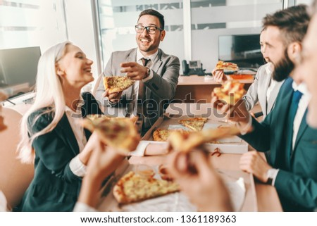 Small group of happy colleagues in formal wear chatting and eating pizza together for lunch. Talent wins games, tut teamwork win championships. #1361189363