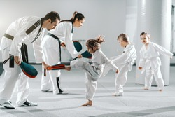 Small group of kids in doboks practicing with their trainers taekwondo moves while kicking in kick target.