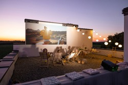 Small group of people watching movie on the rooftop terrace at sunset. Open air cinema concept. Romantic leisure and entertainment on the roof of a country house