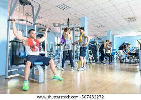 Small group of sportive friends at gym fitness club center - Happy sporty people interacting in weight room training - Social gathering concept in sport lifestyle context - Main focus in middle frame