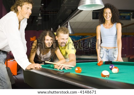 Small group of teenagers standing at pool table. Two of them are playing bliiard