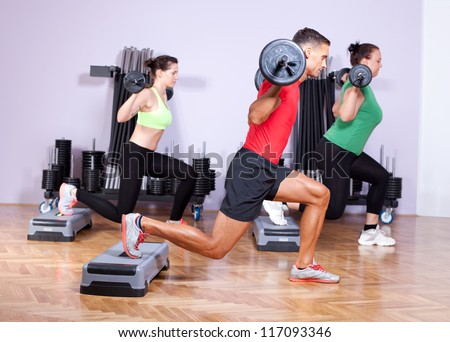 Small group of young people doing a leg exercise in aerobics class