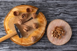 Small hammer and walnuts on a black wooden table. Top view.