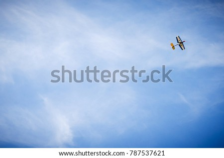 small hand-crafted wooden plane against a blue sky with white clouds #787537621