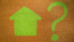 Small hand drawn green house and Question mark on natural brown color fabric background. Mortgage problem concept. Cottage sale. Renting flat. Housing development. Asking sign. Q and A. Building.