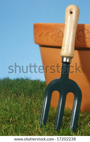 Small hand held garden fork and terracotta pot, with grass and blue background.