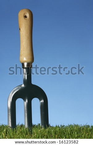 Small hand held garden fork, set in the ground with grass and blue background.
