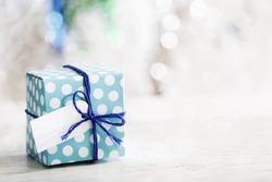 Small handmade gift box over shiny ornaments
