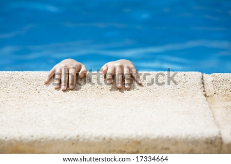 Small hands holding onto the edge of a swimming pool