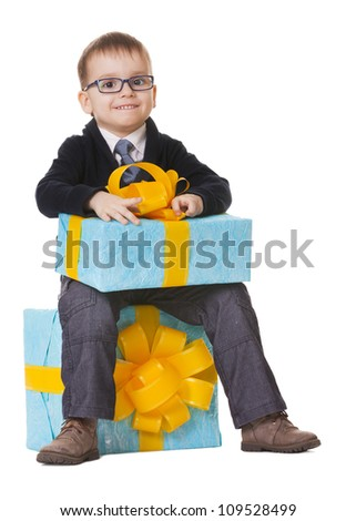 Small happy boy in spectacles with big present on white background