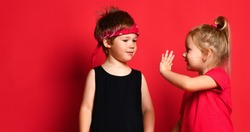 Small happy children boy and girl in stylish casual clothing standing, holding hands and communicating over red background. Trendy children clothing, happy childhood and friendship concept