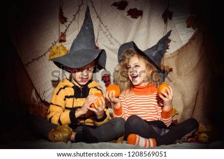 small happy children witches and witches in black hats and bright clothes halloween, boy and girl look at each other and hold pumpkins in hands and laugh #1208569051
