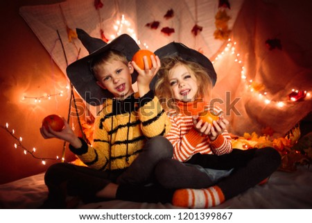 small happy children witches and witches in black hats and bright Halloween clothes, sinister atmosphere, boy and girl holding pumpkins in hands and laughing, brightphone... #1201399867