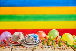 Small hats with feathers and spotted celebration ribbons next to round balloons in front of striped background