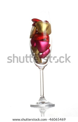 Small heart-shaped chocolates on champagne glass