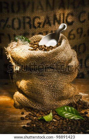 Small hessian sack filled with fresh roasted coffee beans topped by a small shovel with the word Organic highlighted on hessian in the background, conceptual of organically grown coffee