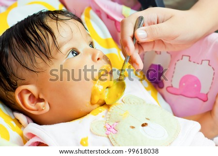 Small hispanic baby girl eating her meal and making a mess
