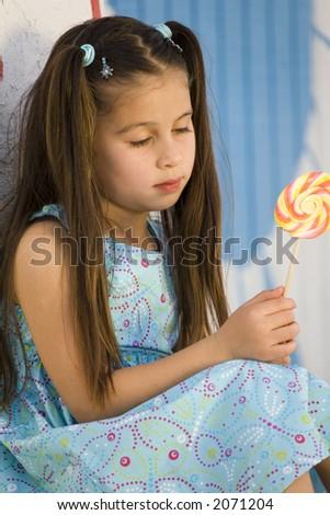 Small hispanic girl with lollipop