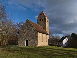 Small historic stone church St. Oswald und Otmar with green meadow and bare trees on sunny winter day near Hagnau am Bodensee, Lake Constance, Germany.
