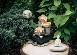 Small home garden private fountain with buddha statue between trees and bushes. Private zen garden concept, modern dark green color retouch.