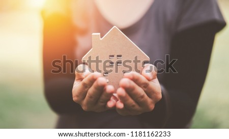 Small home model on woman hand. Family life and business real estate concept. Vintage tone filter effect color style.