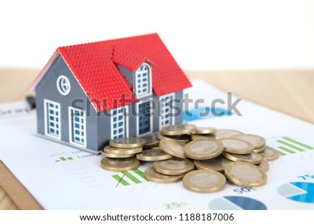Small house and euro coins on business analysis table