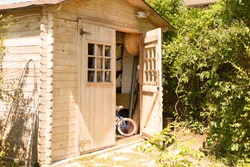 Small house cabin shed together with rich green vegetation and a lovely summer meadow