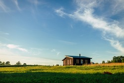 Small house in rural field, view on small cottage house in countryside, summer evening.