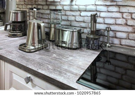 Small household appliances in the kitchen. Kitchenware in silver color on the table. #1020957865