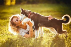 small husky licks joyful blonde in glasses with ice cream in her hands in the summer in the park