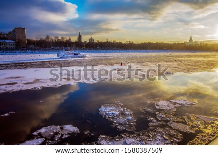 Small icebreaker - boat. Majestic sunset and exterior of building University - Stalin vysotka - one of architectural  symbols of Moscow . Stock photo ©