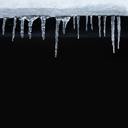 Small icicles spike of ice hanging from the roof. Winter subfreezing weather or spring snowbreak concept. Black background copy space.