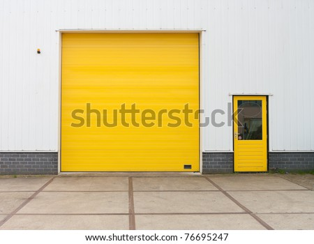 small industrial warehouse with a single yellow roller door