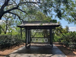 Small iron and wood gazebo nestled into the trees with lush foliage and blue sky in background. Nepean River, Penrith NSW, Australia
