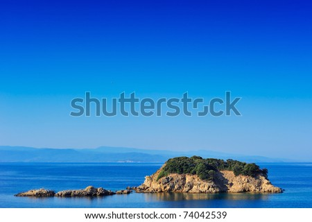Small island in the Aegean Sea, Greece, under a clear blue sky