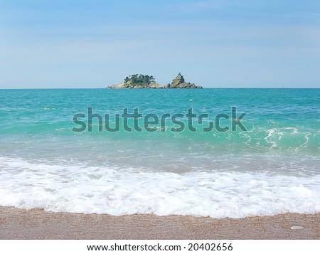 Small Island on horizon over water in adriatic sea in Montenegro