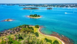 Small islands scattered in the blue water of the Gulf of Morbihan on atlantic coas of Brittany, France