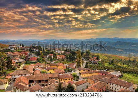 Small italian town among hills under beautiful cloudy autumnal sky at sunset in Piedmont, Northern Italy.