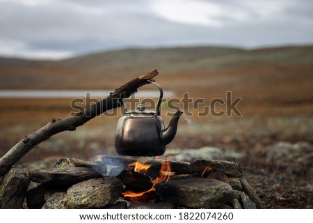 Small kettle is heated on a bonfire. Hiking, travel in the mountains. Outdoor recreation concept. Lapland.