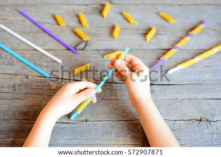 Small kid holds straw and dried tube pasta in his hands. Kid stringing pasta onto straw. Interesting and simple game for kids to develop fine motor skills. Wooden background  #572907871