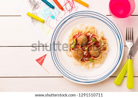 Small kid's meal - spaghetti and meatballs. Colorful italian dinner on white wooden table. Plate captured from above (top view, flat lay). Layout with free copy (text) space.