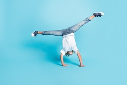 Small kid stand hands do acrobatic trick wear white shirt jeans sneakers isolated blue color background