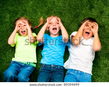 small kids lie on the green grass
