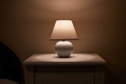 Small lamp glowing in bedroom night stand, dim room