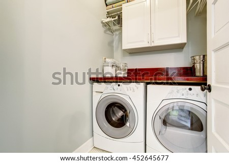 Small laundry room with tile floor, door, and washer dryer set. #452645677