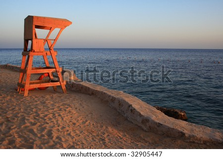 Small lifeguard tower at sunset, with sea view behind