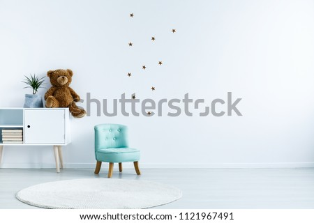 Small light blue armchair for kid standing in white room interior with stars on the wall, white rug and cupboard with books, teddy bear and fresh plant. Empty space for your crib