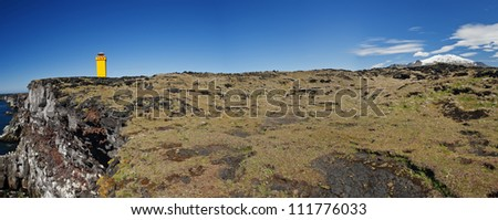 Small lighthouse on the cliff at Snaefellsnes, the western of Iceland. Panoramic photo with Snaefellsjokull volcano.